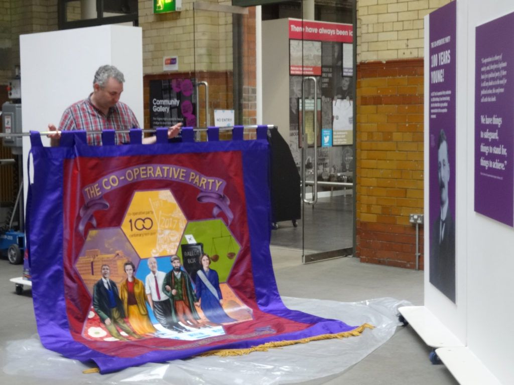 The PHM team prepare to hang the centenary banner